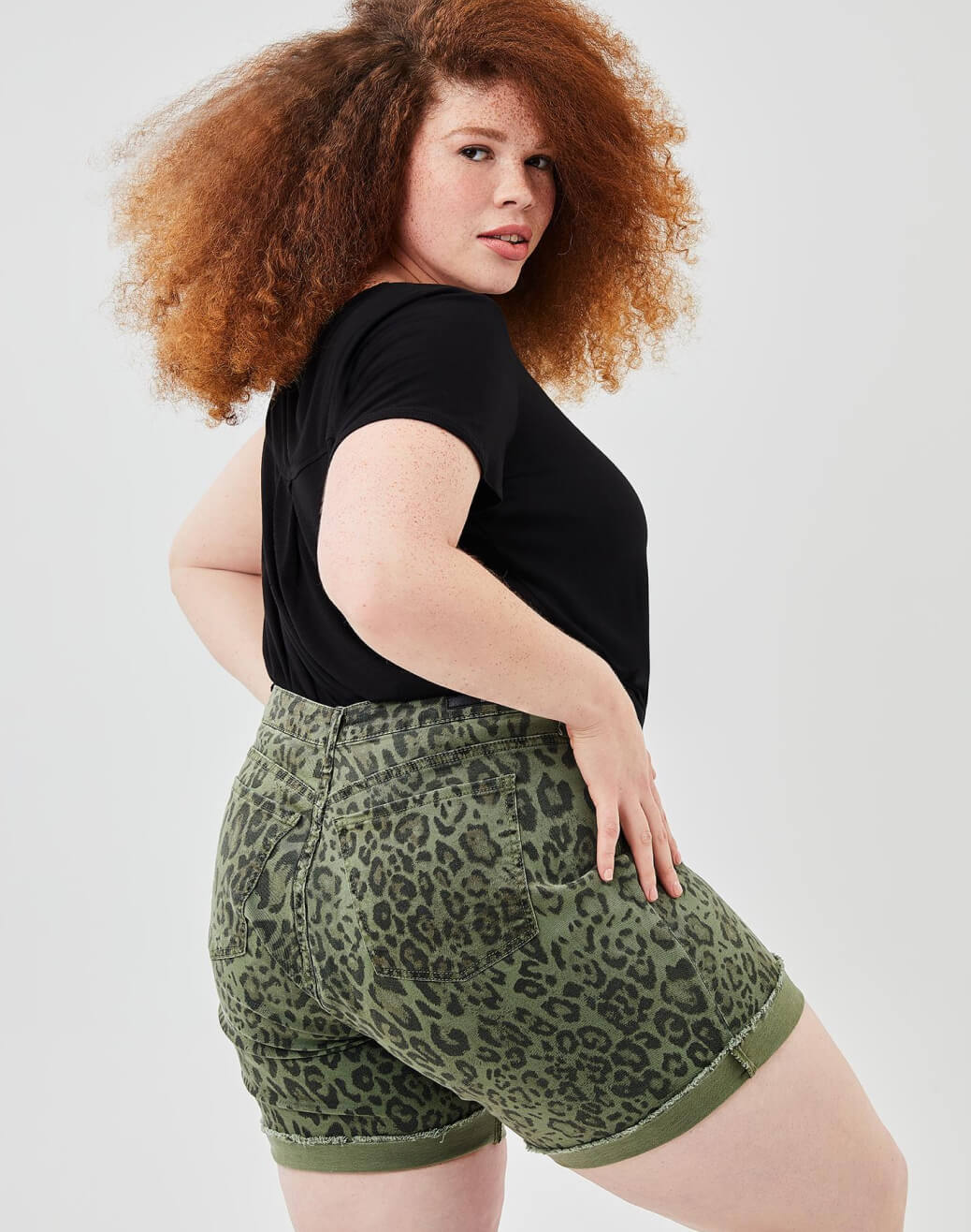 Woman in plus-size leopard print shorts and plus-size black top.