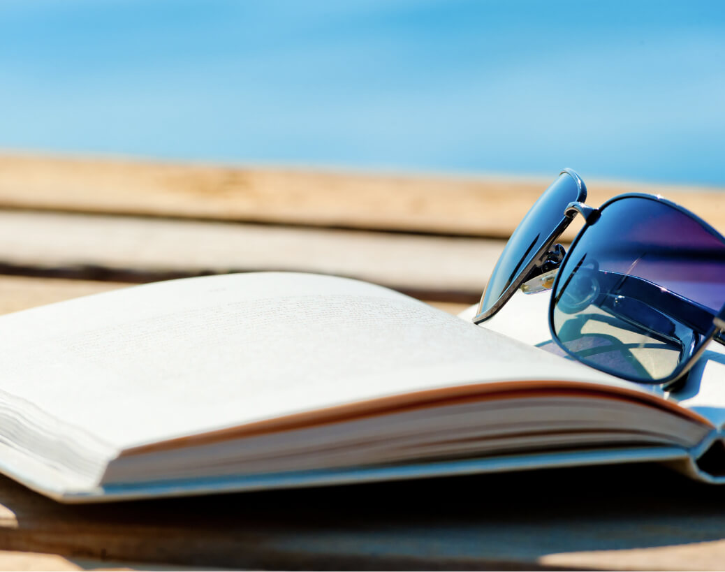 Open book and sunglasses sitting on a dock