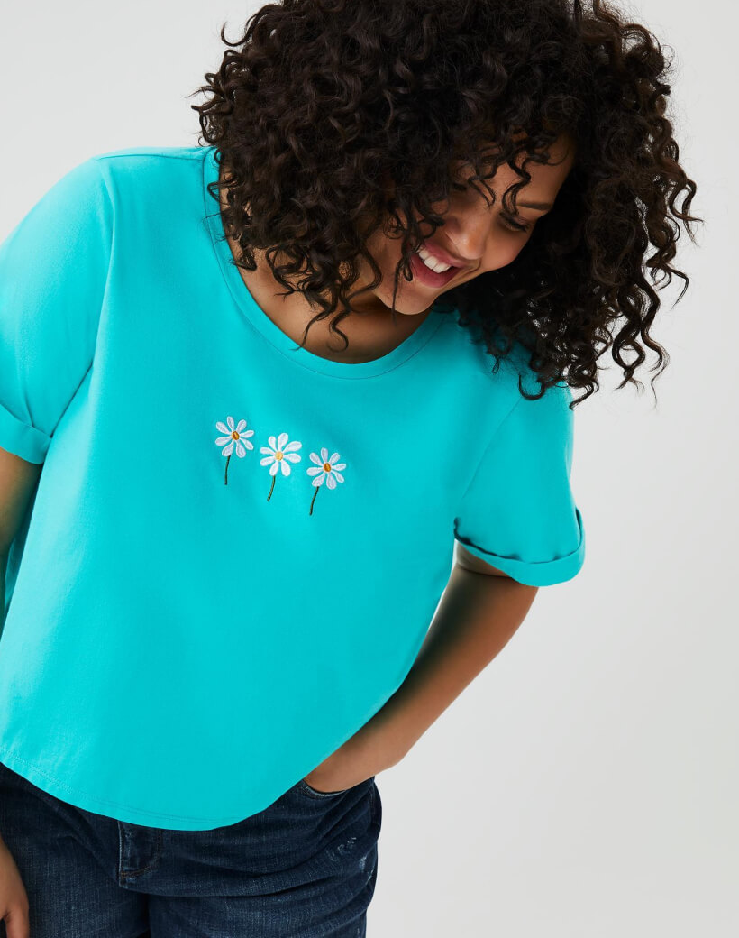 Woman in plus-size blue t-shirt with flowers.